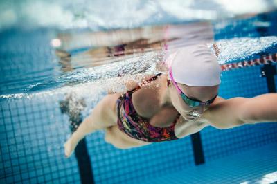 Schwimmerin unter Wasser im Schwimmbecken